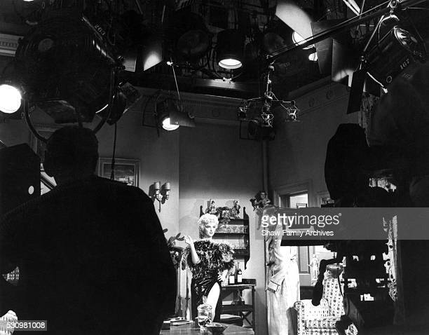 Marilyn Monroe wearing a feather boa with costar Tom Ewell with cameras and equipment in the foreground during the filming of 'The Seven Year Itch'...
