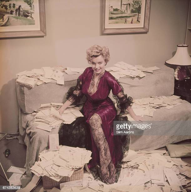 Marilyn Monroe , wearing a red negligee trimmed with black lace, sorts out her fan mail shortly after her film 'The Asphalt Jungle' had been...