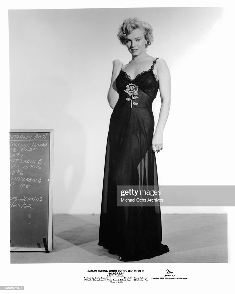 Marilyn Monroe wearing a sheer evening gown and standing next to a ...