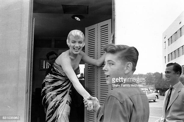 Marilyn Monroe wearing a tigerstriped dress shakes hands with a boy on set in 1954 during the filming of 'The Seven Year Itch' in Los Angeles...