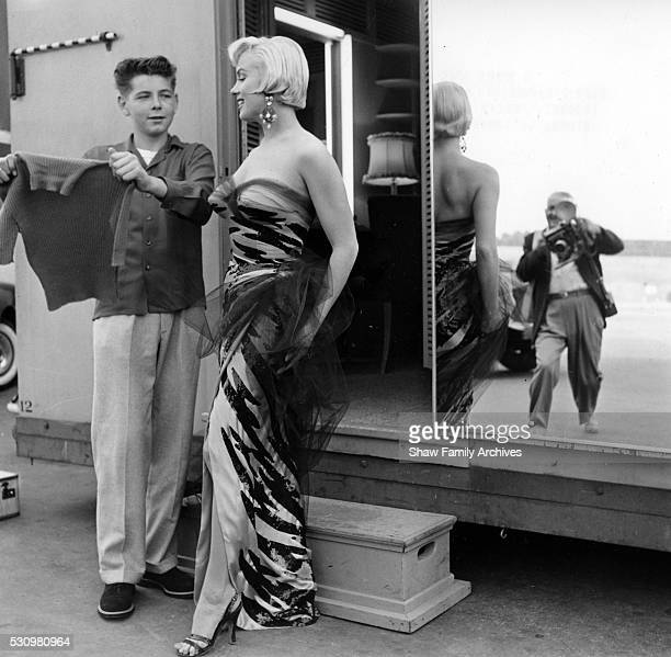 Marilyn Monroe wearing a tigerstriped dress talks to a boy on set with the photographer Frank Powolny visible in the mirror in 1954 during the...