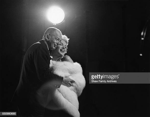 Marilyn Monroe wearing a white fur stole wrap with director Billy Wilder on set for a publicity photo shoot with Richard Avedon in his studio during...