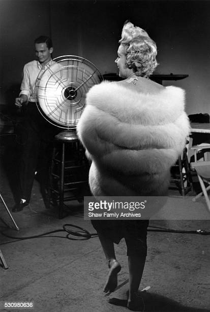 Marilyn Monroe wearing a white stole fur wrap prepares for a publicity photo shoot with Richard Avedon in his studio in 1954 during the filming of...