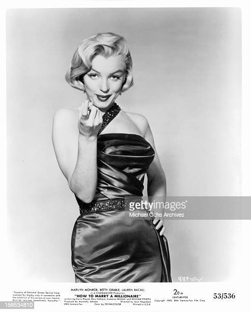 Marilyn Monroe with a come hither look on her face wearing a satin sexy dress in a scene from the film 'How To Marry A Millionaire' 1953