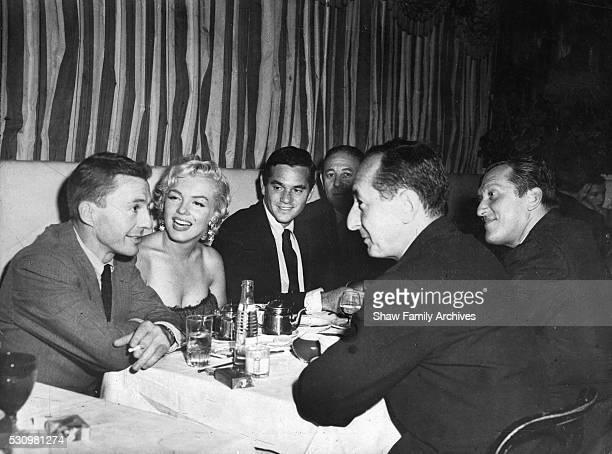 Marilyn Monroe with actor David Wayne photographer Milton Greene newspaper columnist Leonard Lyons and playwright Sidney Kingsley at the 'Little...