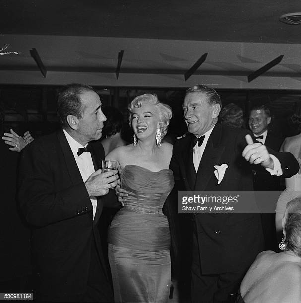 Marilyn Monroe with actors Humphrey Bogart and Clifton Webb at the wrap party for the filming of The Seven Year Itch at Romanoff's Restaurant in 1954...