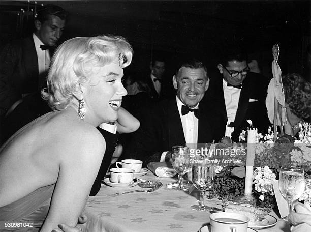 Marilyn Monroe with Clark Gable and newspaper columnist Sidney Skolsky at the wrap party for the filming of 'The Seven Year Itch' at Romanoff's...