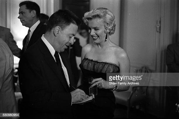 """Marilyn Monroe with co-star Tom Ewell and newspaper columnist Earl Wilson at a press party for """"The Seven Year Itch"""" in 1954 in New York, New York."""