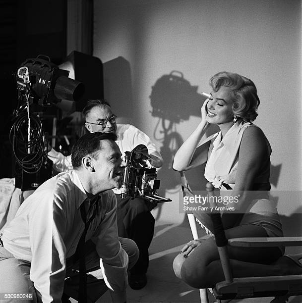 """Marilyn Monroe with co-star Tom Ewell and photographer Frank Powolny in 1954 during the filming of """"The Seven Year Itch"""" in Los Angeles, California."""