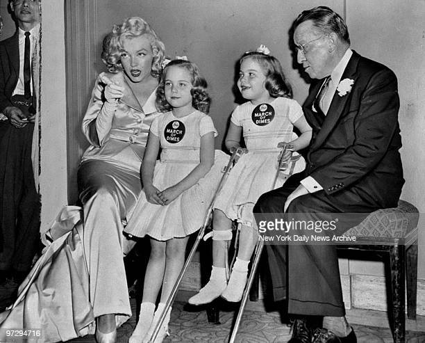 Marilyn Monroe with March of Dimes poster children Linda Lou and Sandy Sue and Basil O'Connor of the Polio Foundation at the 14th Annual March of...