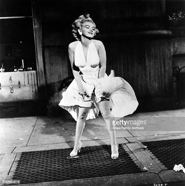 Marilyn Monroe with the skirt of her white dress blowing as she stands over a subway grate on set in 1954 during the filming of 'The Seven Year Itch'...