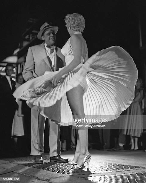 Marilyn Monroe with the skirt of her white dress blowing as she stands over a subway grate at the corner of 51st Street and Lexington Avenue with...