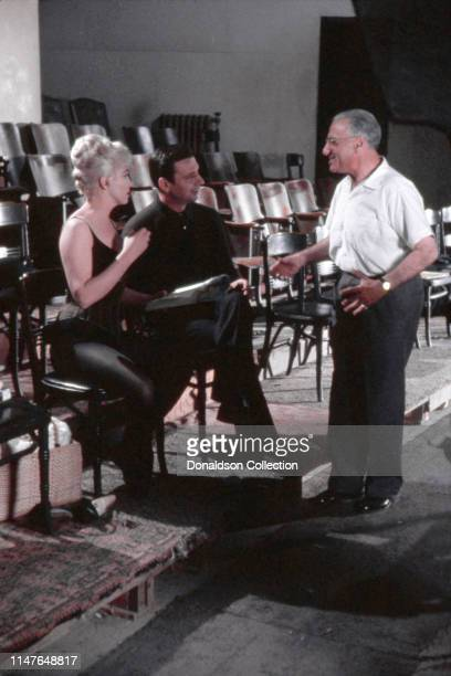 Marilyn Monroe Yves Montand and director George Cukor on the set of the movie Let's Make Love in 1960 in California