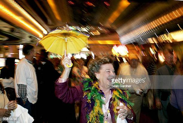 Marilyn Reynolds of Metairie, Louisiana twirls her umbrella while doing a second line into Harrah's Casino during itOs reopening in New Orleans,...