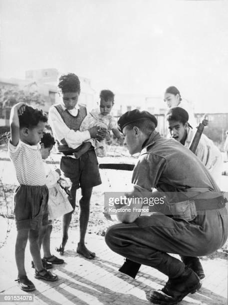 Marin anglais discutant avec des enfants à PortSaïd Egypte le 22 novembre 1956