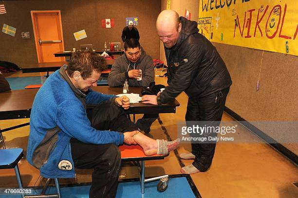 Marin Buser shows his swollen ankle to Aaron Burmeister in the school cafeteria during the 2014 Iditarod Trail Sled Dog Race on Tuesday March 4 in...