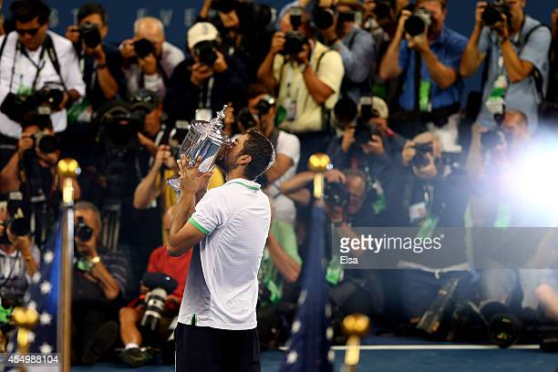 Marin Cilic of Croatia celebrates with the trophy after defeating Kei Nishikori of Japan to win the men's singles final match on Day fifteen of the...
