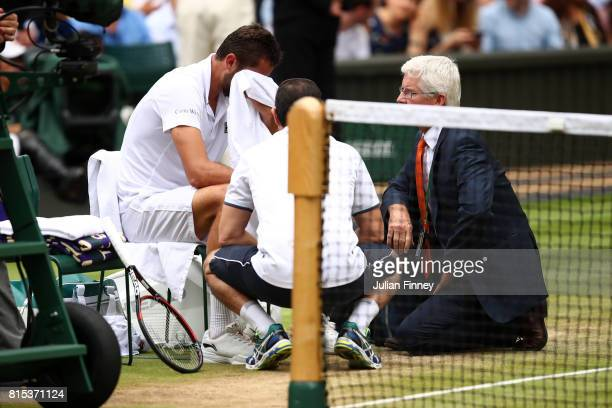 Marin Cilic of Croatia is given assistance during the Gentlemen's Singles final against Roger Federer of Switzerland on day thirteen of the Wimbledon...