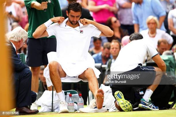 Marin Cilic of Croatia is given treatment during the Gentlemen's Singles final against Roger Federer of Switzerland on day thirteen of the Wimbledon...