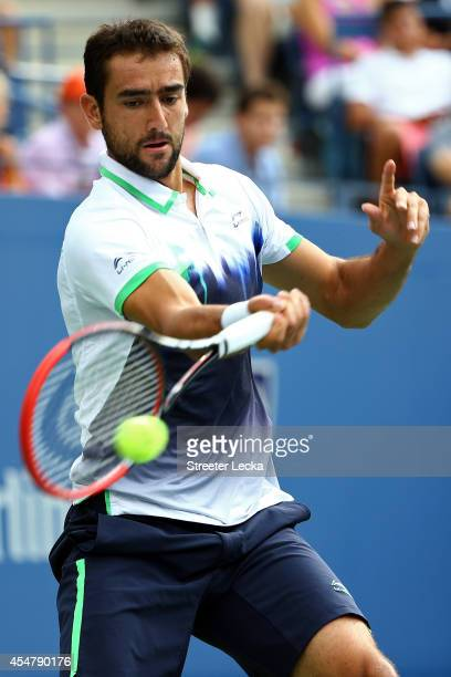 Marin Cilic of Croatia returns a shot against Roger Federer of Switzerland during their men's singles semifinal match on Day Thirteen of the 2014 US...