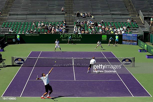 Marin Cilic of Croatia serves to Marcel Granollers and Marc Lopez of Spain while playing with Lukas Dlouhy of Czech Republic during the Sony Open at...