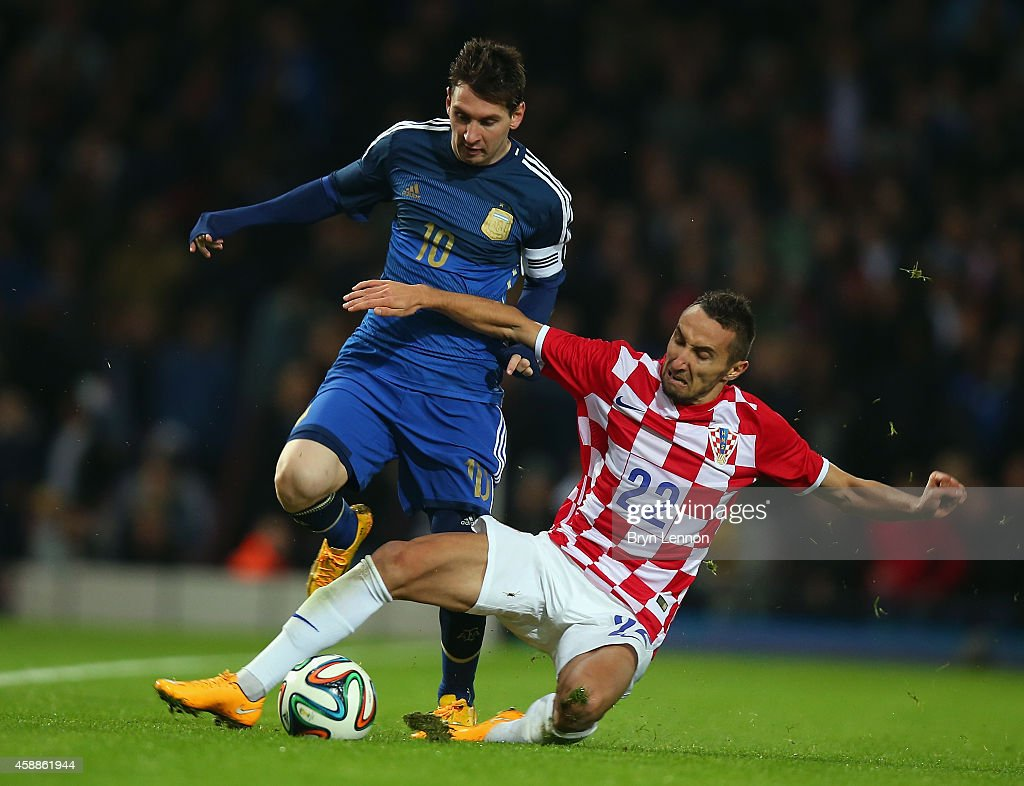 Marin Leovac of Croatia tackles Lionel Messi of Argentina during the International Friendly between Argentina and Croatia at Boleyn Ground on November 12, 2014 in London, England.