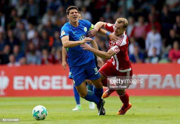 Marin Mandic of Norderstedt and Mario Gomez of Wolfsburg battle for the ball during the DFB Cup first round match between FC Eintracht Norderstedt...
