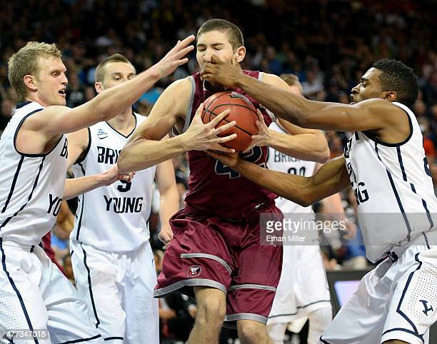 Marin Mornar of the Loyola Marymount Lions and Tyler Haws and Anson Winder of the Brigham Young Cougars go after a loose ball during a quarterfinal...