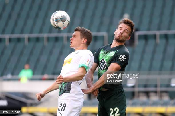 Marin Pongracic of VfL Wolfsburg and Matthias Ginter of Borussia Moenchengladbach compete for a header during the Bundesliga match between Borussia...