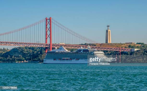 Marina an Oceaniaclass cruise ship operated by Oceania Cruises sails past the National Sanctuary of Christ the King and the 25 de Abril bridge on the...