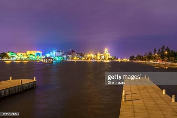 Marina and buildings on waterfront at night, Xiamen, Fujian, China