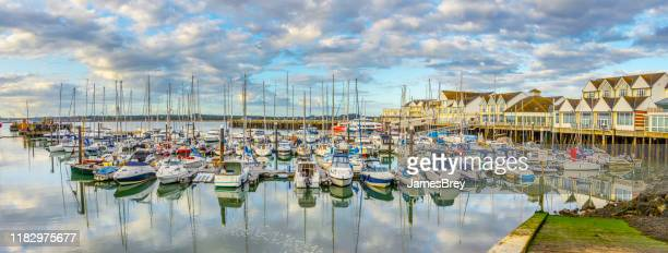 marina and harbor in southampton, uk, with tranquil waters reflecting clouds, sky. - southampton england stock pictures, royalty-free photos & images