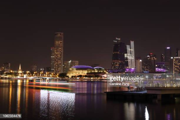 marina bay at night with light trails of colourful river boat and water reflections. - caroline pang stock pictures, royalty-free photos & images