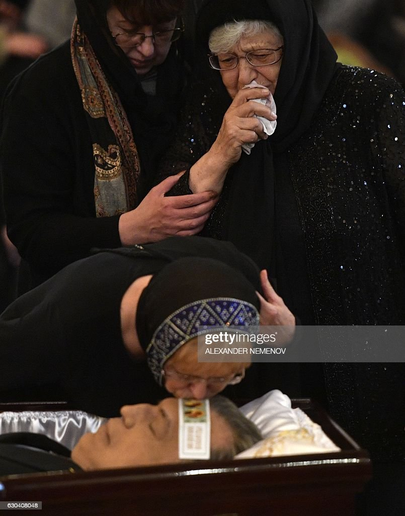 Marina Davydova Karlova (C), the widow of killed Russian ambassador to Turkey, Andrei Karlov, and his mother Maria (R) pay their respects during the funeral ceremony at the Christ the Savior Cathedral in Moscow on December 22, 2016. President Vladimir Putin on December 22, 2016 bade farewell to Andrei Karlov at a packed memorial ceremony in Moscow for the diplomat who was assassinated in Turkey by an off-duty policeman. / AFP / Alexander NEMENOV