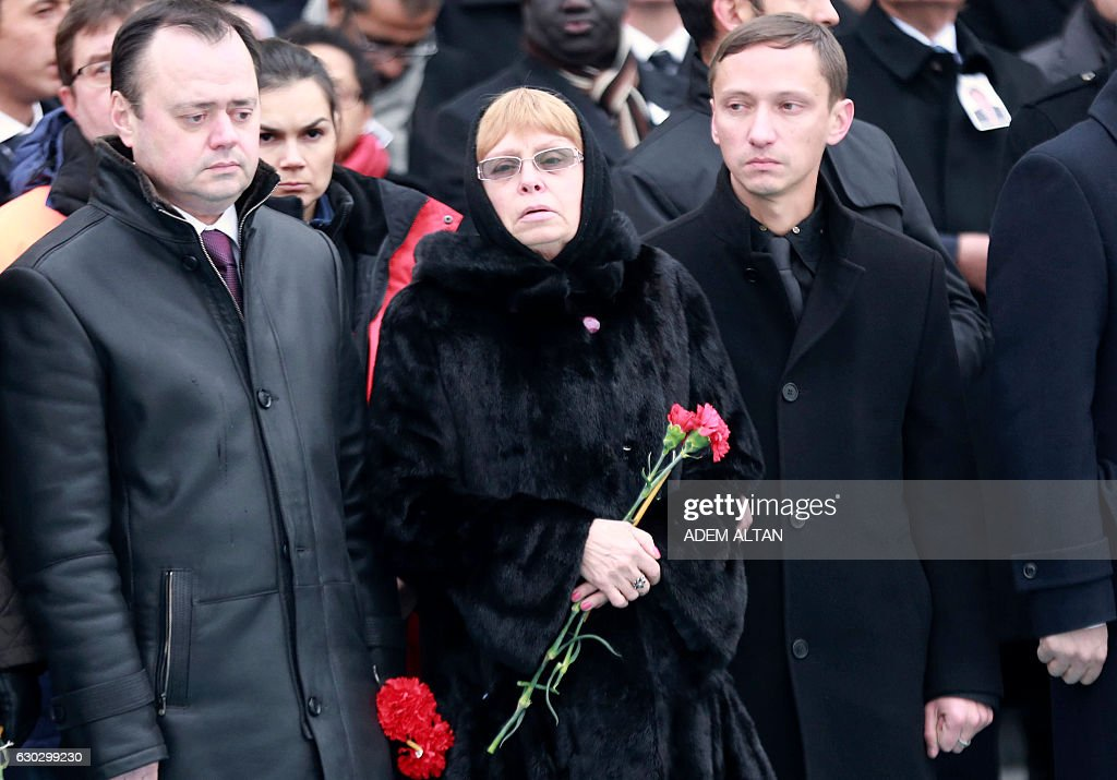 Marina Davydova Karlova, (C) widow of Russian Ambassador to Turkey Andrei Karlov, stands during a ceremonial farewell with full state honours on the tarmac of Ankara's Esenboga Airport in Ankara on December 20, 2016, before the coffin is transported on a Russian plane for Moscow. Veteran diplomat Andrei Karlov was shot nine times in the back by an off-duty Turkish policeman at the opening of an exhibition of Russian photography on December 19, 2016. The brazen killing stunned Ankara and Moscow, which have rowed repeatedly over the Syria conflict but in recent weeks have begun cooperating closely on the evacuations from war-wrecked Aleppo. / AFP / ADEM