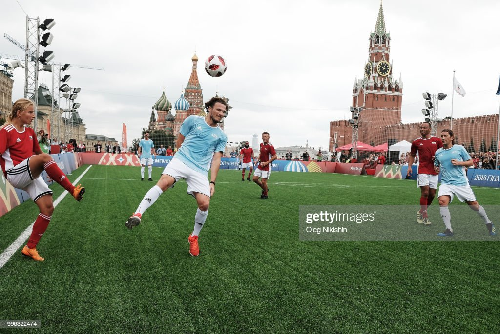 Marina Fedorova (L) and Diego Forlan (C) compete during the Legends Football Match in 'The park of Soccer and rest' at Red Square on July 11, 2018 in Moscow, Russia.