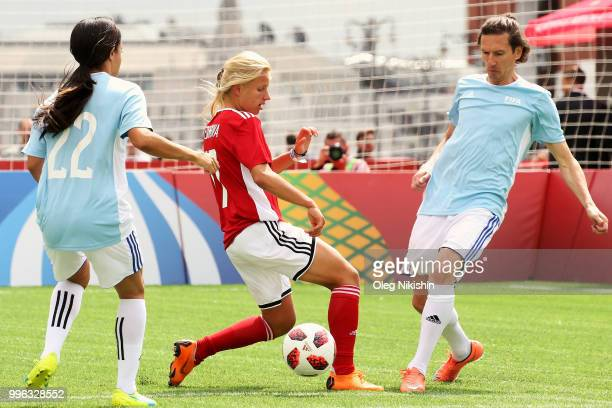 """Marina Fedorova competes for the ball with Alexey Smertin during the Legends Football Match in """"The park of Soccer and rest"""" at Red Square on July..."""
