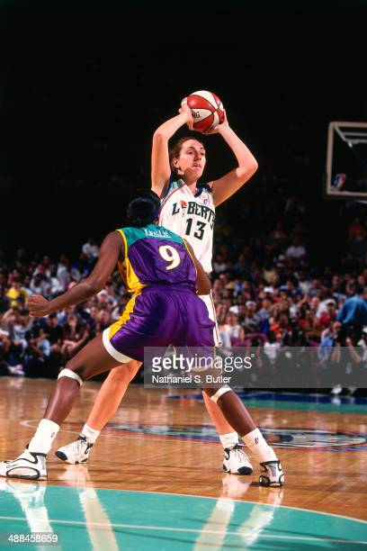 Marina Ferragut of the New York Liberty looks to pass against Lisa Leslie of the Los Angeles Sparks the on June 23 2000 at Madison Square Garden in...