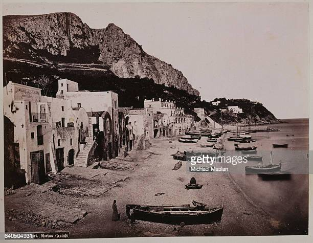 Marina Grande on the island of Capri ca 1890s Several boats are anchored near the shore and pulled up on the beach A row of white adobe houses lines...