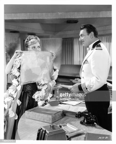 Marina Koshetz looking through lace handkerchief at George Brent in a scene from the film 'Luxury Liner' 1948