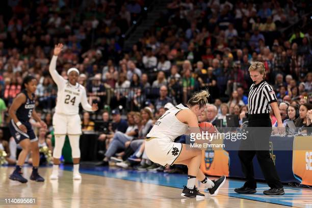 Marina Mabrey of the Notre Dame Fighting Irish attempts to save the ball from going out of bounds against the UConn Huskies during the fourth quarter...