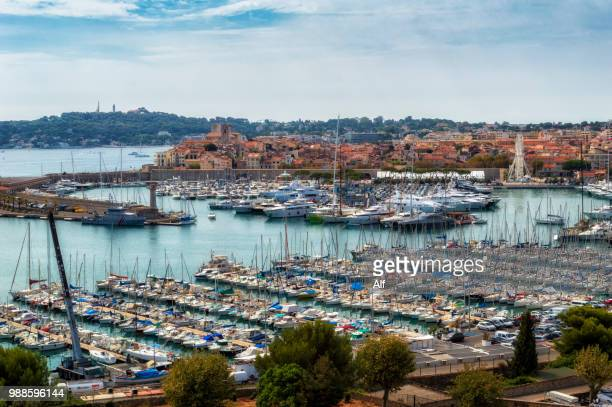 marina of antibes in the foreground and the old town of antibes in the background, french riviera, france - antibes stock photos and pictures