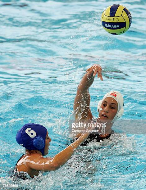Marina Radu of Canada passes the ball over Cecilia Canetti of Brazil in the Women's Preliminary Round Group B Water Polo match between Canada and...
