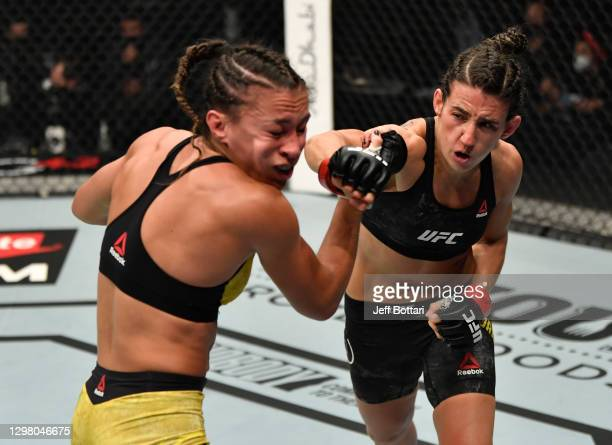 Marina Rodriguez of Brazil punches Amanda Ribas of Brazil in a strawweight fight during the UFC 257 event inside Etihad Arena on UFC Fight Island on...
