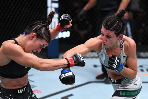 Marina Rodriguez of Brazil punches Mackenzie Dern in their women's strawweight bout during the UFC Fight Night event at UFC APEX on October 09, 2021...