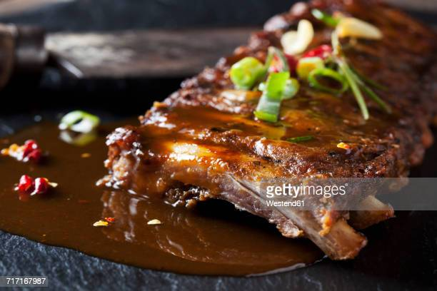 marinated and grilled spare ribs with barbecue sauce on slate - barbeque sauce stock photos and pictures