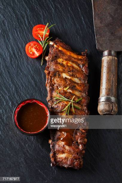 marinated and grilled spare ribs with bowl of barbecue sauce on slate - barbeque sauce stock photos and pictures