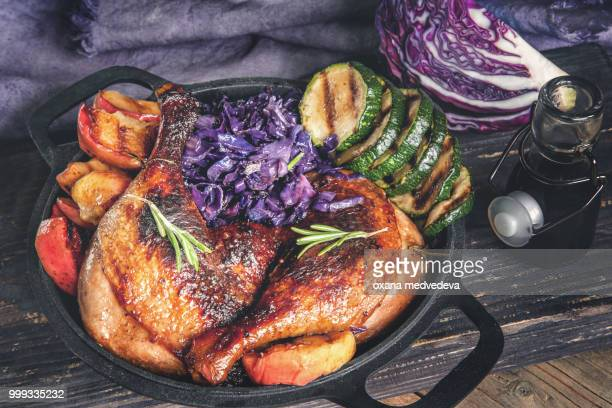Marinated pieces of duck grilled with red cabbage, onions and apples grilled and served in a...