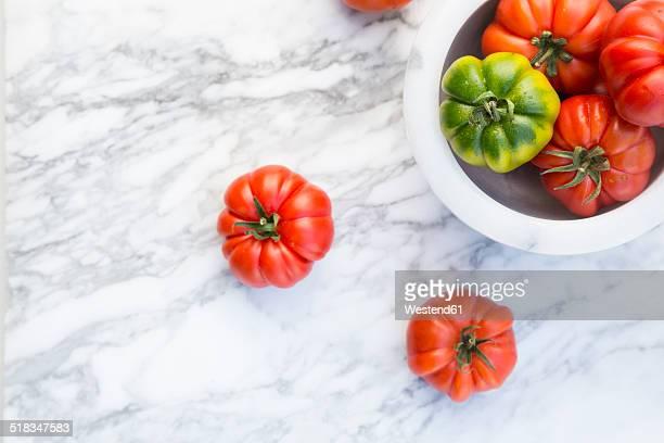 Marinda tomatoes in bol on marble plate