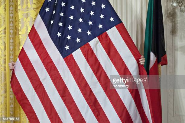 A US Marine adjusts the American flag ahead of a news conference with US President Donald Trump and Sheikh Sabah AlAhmed AlSabah Kuwait's emir not...